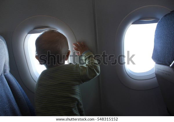 A child is looking out a window from an airplane seat.