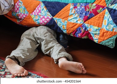 Child looking for something under the bed.