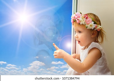 the child is looking in the spring window