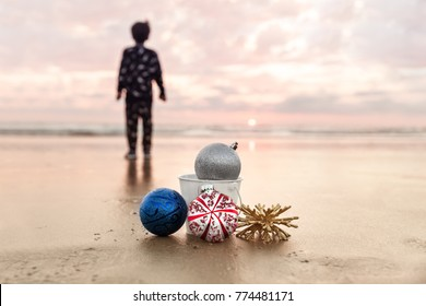 Child Looking at Sunset at Carlsbad State Beach and Christmas Decorations on the background of Sea in San Diego, Winter Holiday Concept, Selective Focus