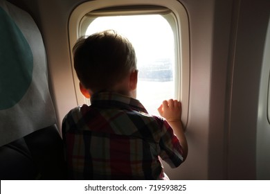 Child looking through porthole in an airplane