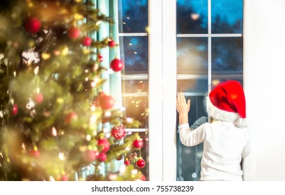 Child looking to the window waiting for Santa, decorated and illuminated Christmas tree.