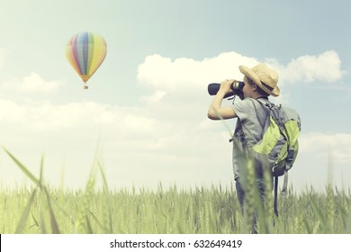 Child looks curious with his binoculars a hot air balloon flying in the sky