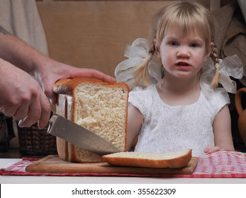 The child looks like sliced bread. On the table freshly baked bread. Male hand cut bread with a large knife. A huge loaf of white bread and a little girl with two plaits.
