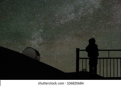 A child looks at the night sky with the Milky Way and a telescope dome on the horizon.