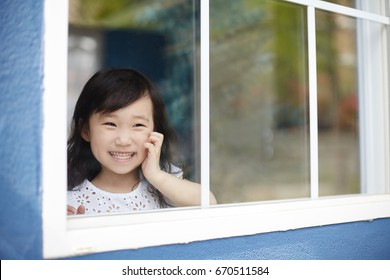 A child looks out the window.  Beautiful little girl smiling and watching out the window.