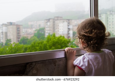 The child looks out the window. Lonely child