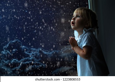 the child looks out the window on Christmas day
