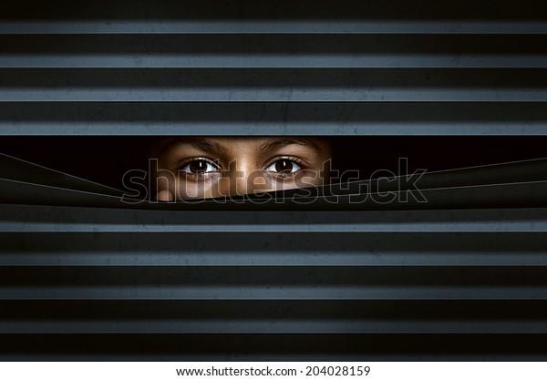 Child looks through window blinds