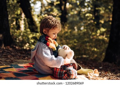 Child love. Atumn fun at the park. Happy kids autumn. Cute boy with Autumn Leaves on Fall Nature Background