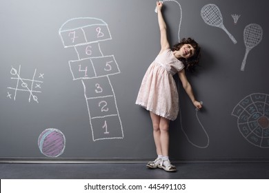 Child loves to be active and smiles while doing sports. Depicted childish favorite games like hopscotch, badminton and jumping rope on the neutral background in the studio.