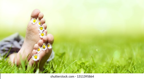 Child lying barefoot in the grass in spring