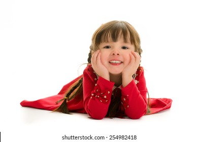 Child lying down with hands on face.