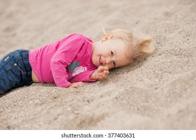 child is lying on the beach