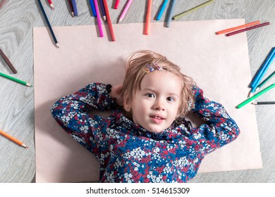 Child lying on the floor on paper near crayons. Little girl painting, drawing. Top view. Creativity concept.