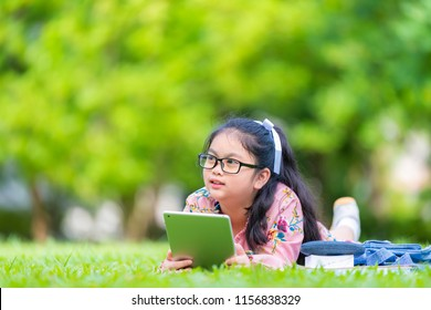 Child is lying on the grass with tablet. Girl playing with a digital tablet or watching a movie or listening to music outdoors.