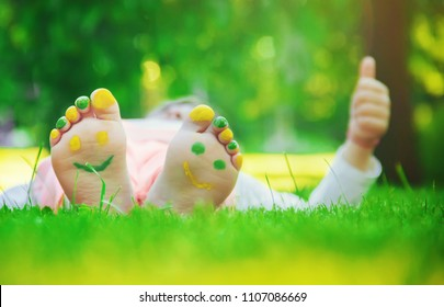 Child lying on green grass. Kid having fun outdoors in spring park. Selective focus.