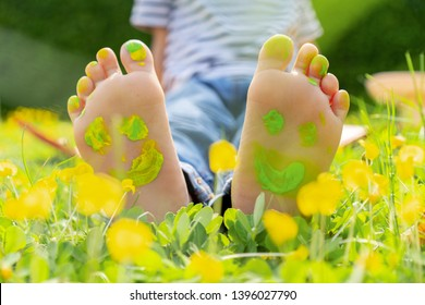 Child lying on green grass. Kid having fun outdoors in spring park. Child feet with painting smiles lying on green grass