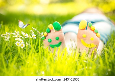 Child lying on green grass. Kid having fun outdoors in spring park