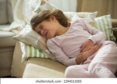 Child lying on sofa in the living room with stomach pain. Hands on belly. Little girl suffering