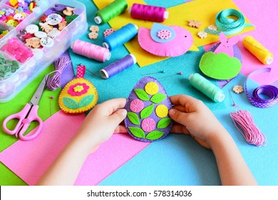 Child made a felt Easter egg ornament. Small child holds a felt Easter egg ornament in his hands. Easter crafts, craft tools and materials on a table. Festive spring crafts concept