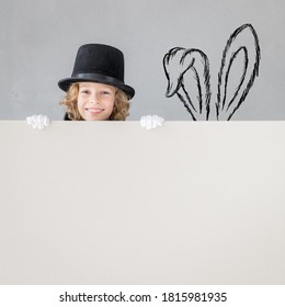 Child magician hiding behind banner blank. Happy kid holding cardboard background with copy space