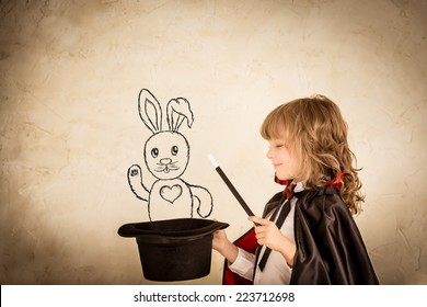 Child magician holding a top hat with drawn rabbit against grunge background. Focus on the hat