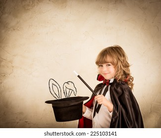 Child magician holding a top hat with drawn rabbit against grunge background