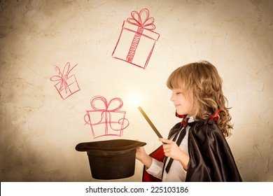 Child magician holding a top hat with drawn gift boxes. Christmas holiday concept