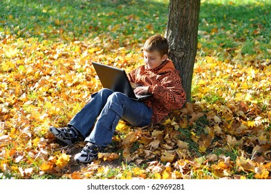 Child make fun with notebook under tree in autumn forest