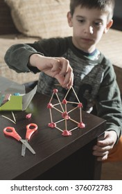 Child make house with wooden sticks and plasticine