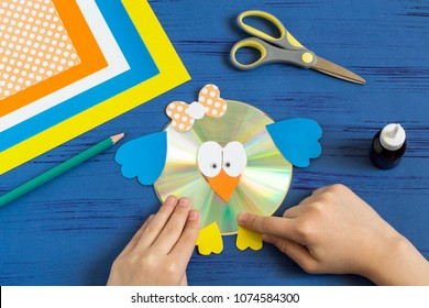 Child makes bird from CD. Children's art project. DIY concept. Step-by-step photo instruction. Step 14. Child glues paws on CD