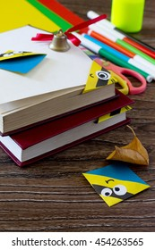 The child makes the book bookmark cartoon character mignon. Glue, scissors, paper and autumn leaves on a wooden table. Copy space. Children's art project, a craft for children.