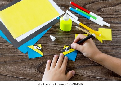 The child makes a book with a bookmark mignon. The child draws the details of paper products. Made with his own hands. Children's art project, a craft for children.