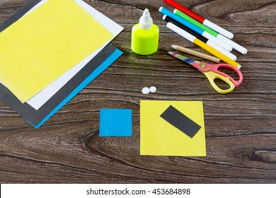 The child makes a book with a bookmark mignon. The child draws the details of paper products. Glue, paper, scissors on a wooden table. Children's art project, a craft for children.