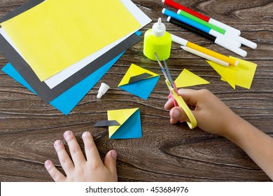 The child makes a book with a bookmark mignon. The child carves the details of paper products. Glue, paper, scissors on a wooden table. Children's art project, a craft for children.