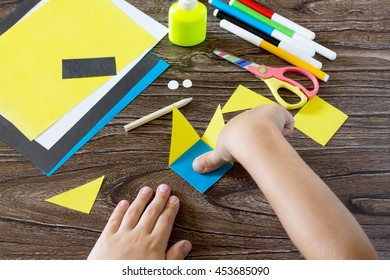The child makes a book with a bookmark mignon. The child bonded items paper products. Glue, paper, scissors on a wooden table. Children's art project, a craft for children. Craft for kids.