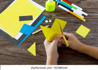 The child makes a book with a bookmark mignon. The child carves the details of paper products. Glue, paper, scissors on a wooden table. Children's art project, a craft for children. Craft for kids.
