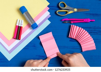 Child makes bunnies out of paper for Easter decoration. Creative idea for children's party. DIY concept. Step by step photo instruction. Step 2. Fold paper accordion