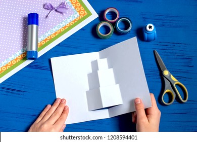 Child makes card with 3D gifts for Christmas. Children's art project. DIY concept. Step by step photo instruction. Step 5. Expand postcard