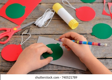 Child makes Christmas balls out of cardboard. Child draws a ball on a cardboard with a template and a pencil. Step. Stationery on the table. Easy Christmas crafts and activity for kids idea