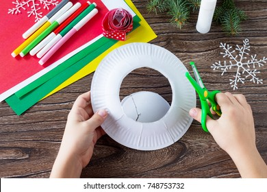A child makes a Christmas wreath with a candle. Made by own hands. Children's art project for children. Craft for kids.