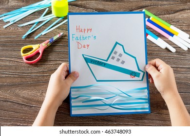 The child makes crafts out of paper boats. Greeting card for on Father's Day. Made with his own hands. Children's art project, a craft for children. Craft for kids.