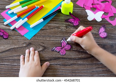 The child makes decoration paper paper butterfly in a glass. Child paints paper part of the product. Glue, paper, scissors on a wooden table. Children's art project, a craft for children.