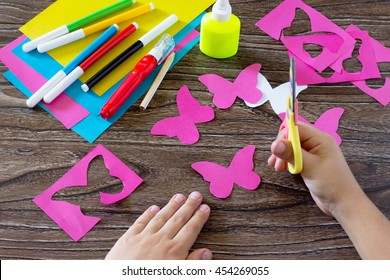 The child makes decoration paper paper butterfly in a glass. Child cuts the paper of the product. Glue, paper, scissors on a wooden table. Children's art project, a craft for children.