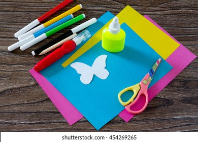 The child makes decoration paper paper butterfly in a glass. Glue, scissors, colored paper and butterfly pattern on a wooden table. Children's art project, a craft for children.