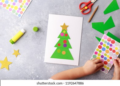 The child makes a greeting card Christmas paper collage. Made with his own hands. Children's art project craft for kids. Craft for children. Top view