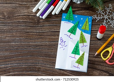 The child makes a greeting card Christmas. Made with his own hands. Children's art project craft for kids. Craft for children. Copy space for your text.