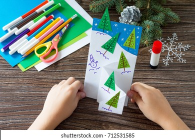 The child makes a greeting card Christmas. Made with his own hands. Children's art project craft for kids. Craft for children.