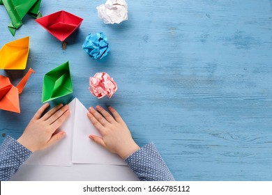 child makes origami from colored paper on a blue table